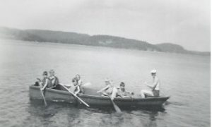 Boys paddling in a rowboat with a man in the stern