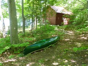 a canoe upside down in front of a cabin