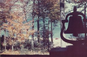 outline of bell in front of the shoreline with fall leaves