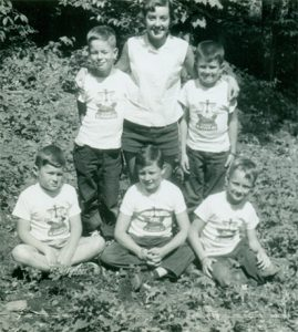 woman with her arms around two boys. Three more boys seated at their feet.