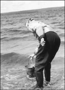 Woman dipping a bucket in a lake