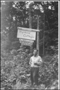 Man standing by a sign for Highland Cottages