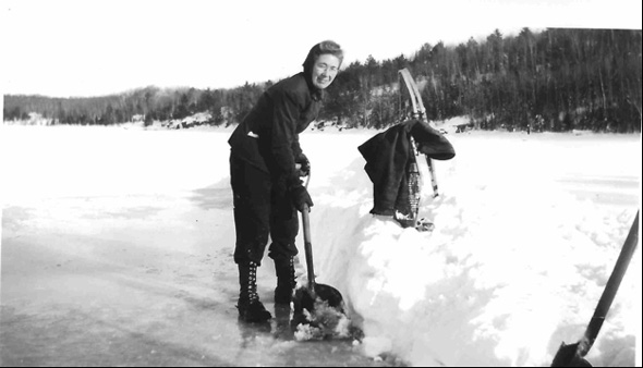 Woman shovelling snow off an iced-over lake