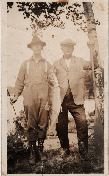 Two men posing with a large fish and a paddle