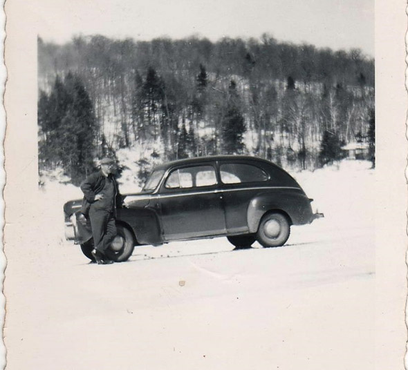 Man poses with car on frozen lake