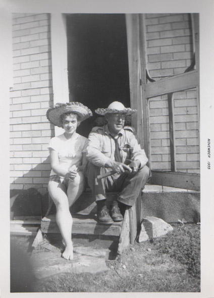 Man and woman in hats pose on a stoop