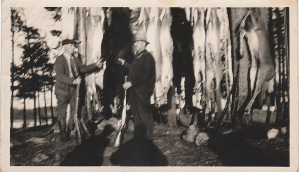 Two men with guns in foreground. Dead deer and bears hanging in the background.