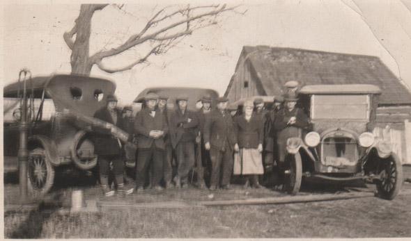 Men posing in front of Model T cars