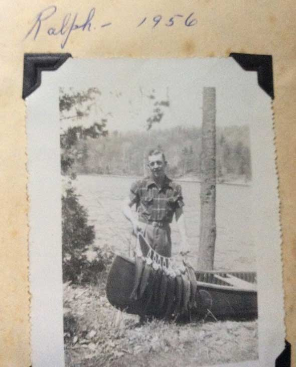 Man standing by a canoe