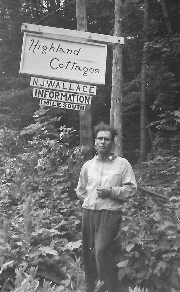 Man standing by a Highland cottages sign