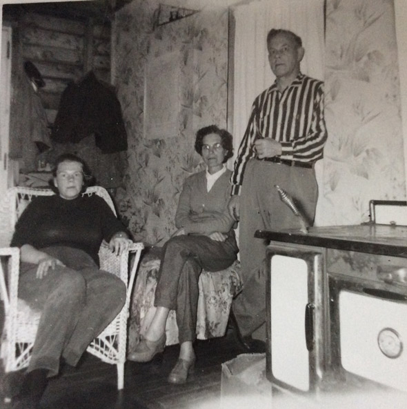 Three white people near an old stove