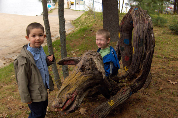 Two boys sitting on driftwood